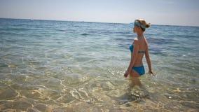 Jeune femme mince entrant dans la mer, eau froide, fille des vacances, concept de touristes banque de vidéos