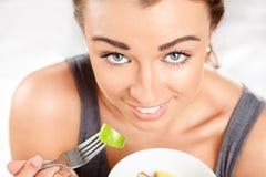 Jeune femme mince mangeant de la salade de fruits photos stock