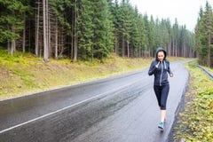 Jeune femme mince pulsant sur la route de montagne images stock
