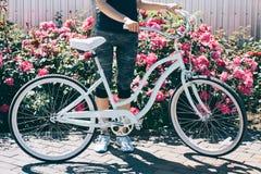 Jeune femme mince se tenant avec la bicyclette sur un fond des buissons Image libre de droits