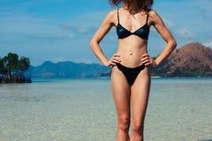 Jeune femme mince se tenant sur la plage tropicale Photographie stock libre de droits