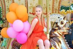 Jeune femme modèle montant un carrousel Photos libres de droits