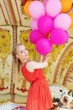 Jeune femme modèle montant un carrousel Image stock