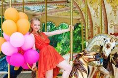 Jeune femme modèle montant un carrousel Image libre de droits