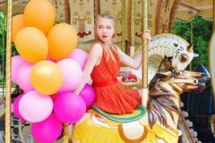 Jeune femme modèle montant un carrousel Photos stock