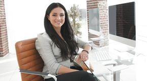 Jeune femme moderne d'affaires s'asseyant au bureau Photos stock