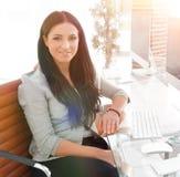 Jeune femme moderne d'affaires s'asseyant au bureau Photographie stock libre de droits