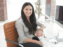 Jeune femme moderne d'affaires s'asseyant au bureau Photographie stock