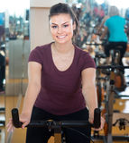Jeune femme montant les bicyclettes stationnaires Image stock