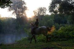 Jeune femme montant un cheval blanc sur un beau paysage Lac clair au brouillard de matin photographie stock libre de droits