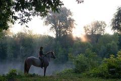 Jeune femme montant un cheval sur un beau paysage Lac clair au brouillard de matin photos libres de droits