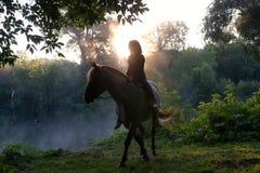 Jeune femme montant un cheval sur un beau paysage Lac clair au brouillard de matin Lever de soleil image libre de droits