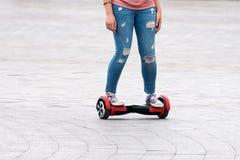 Jeune femme montant un hoverboard sur la place de ville Nouvelles technologies de mouvement et de transport Fermez-vous de l'indi Photographie stock libre de droits