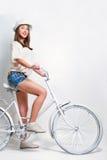 Jeune femme montant un vélo Photo libre de droits