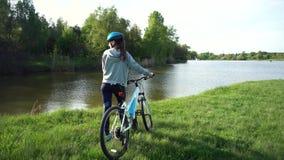 Jeune femme montant un v?lo par le parc sur le fond d'un lac ou d'une rivi?re banque de vidéos