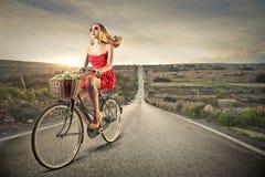 Jeune femme montant un vélo Photographie stock libre de droits