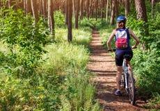 Jeune femme montant une bicyclette dans la forêt Images stock