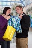 Jeune femme montrant à son ami une chemise tout en faisant des emplettes dans un mail Photographie stock libre de droits