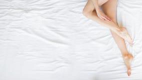 Jeune femme montrant la peau soyeuse lisse après epilation sur le lit à la maison Concept de soins de la peau et d'epilation photos libres de droits