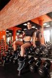 Jeune femme musculaire avec le beau corps faisant des exercices avec l'halt?re image libre de droits