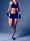 Jeune femme musculaire posant dans les vêtements de sport sur le fond noir image libre de droits