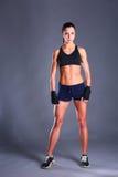 Jeune femme musculaire posant dans les vêtements de sport sur le fond noir photos libres de droits