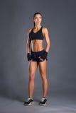 Jeune femme musculaire posant dans les vêtements de sport sur le fond noir Photo stock