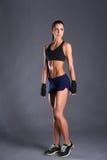 Jeune femme musculaire posant dans les vêtements de sport sur le fond noir Image stock
