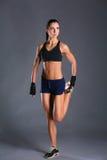 Jeune femme musculaire posant dans les vêtements de sport sur le fond noir Photo libre de droits