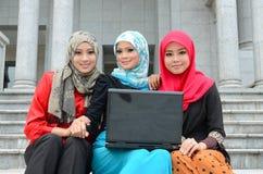 Jeune femme musulmane asiatique dans l'écharpe principale avec l'ordinateur portable image stock