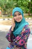 Jeune femme musulmane asiatique dans l'écharpe principale avec le téléphone portable photographie stock