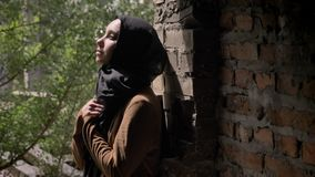 Jeune femme musulmane dans le hijab noir tenant ses mains et regardant vers le haut, se tenant dans l'immeuble de brique abandonn clips vidéos