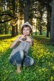 Jeune femme naturelle caucasienne faisant la forme de coeur dans le backli ensoleillé Photo stock