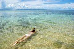Jeune femme naviguant au schnorchel dans l'eau claire sur l'île de Taveuni, Fidji Photos libres de droits