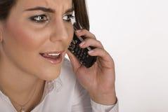 Jeune femme nerveuse parlant au téléphone. images stock