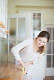 Jeune femme nettoyant la cuisine Images libres de droits