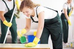 Jeune femme nettoyant la table image libre de droits