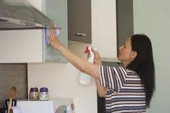 Jeune femme nettoyant les meubles Image stock