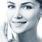 Jeune femme nettoyant son visage par des serviettes Image libre de droits