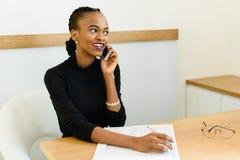 Jeune femme noire de sourire d'affaires au téléphone jetant à notes un coup d'oeil dans le bureau Images stock