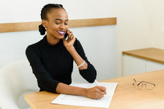 Jeune femme noire de sourire d'affaires au téléphone prenant des notes dans le bureau Photographie stock