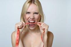 Jeune femme nue mordant une bande de mesure Photo stock