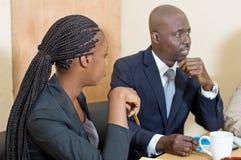 Jeune femme observant son collègue parler lors d'une réunion Photos libres de droits