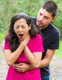 Jeune femme obstruant avec l'homme se tenant derrière exécuter la manoeuvre de heimlich, l'environnement de parc et les vêtements Photographie stock