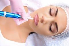 Jeune femme obtenant le maquillage permanent sur des lèvres photographie stock libre de droits