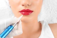 Jeune femme obtenant le maquillage permanent sur des lèvres images libres de droits