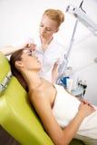 Jeune femme obtenant le traitement de masque de peau de beauté sur son visage avec photographie stock