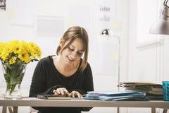 Jeune femme occasionnelle à l'aide du comprimé numérique dans le bureau. Image libre de droits