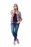 Jeune femme occasionnelle décontractée dans les jeans et la chemise de plaid parlant sur le sourire de téléphone Image stock