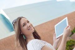 Jeune femme occasionnelle d'affaires à l'aide du comprimé sur une coupure Photos stock